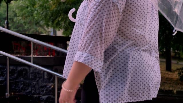 dickes ingwer mädchen mit brille ist station kleine treppe im park bei regenwetter, hält regenschirm - kräftig gebaut stock-videos und b-roll-filmmaterial