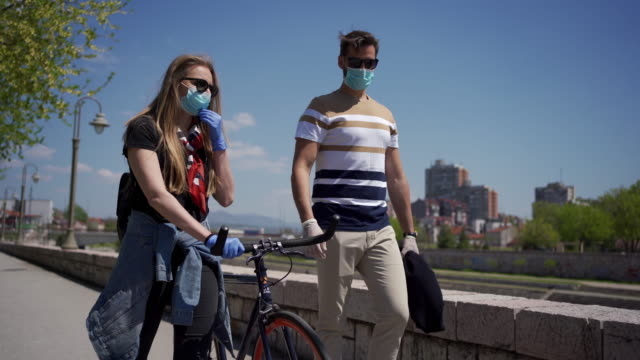 Feeling free after a month of home isolation Young woman pushing her bicycle and taking a relaxing walk with her boyfriend near river while both wearing protective gloves and masks romance stock videos & royalty-free footage