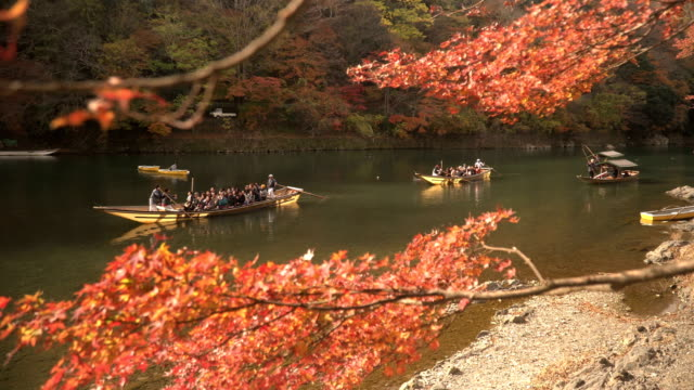 vídeos de stock e filmes b-roll de feeling japanese culture by boat in katsura river amid autumn leaf forest - prefeitura de quioto