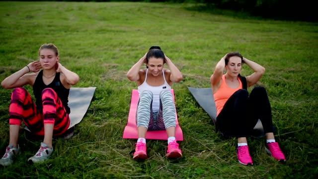 Feeling your abs girls. Group of young athletic people in sportswear doing physical exercises on green grass in summer park outdoors, side view video