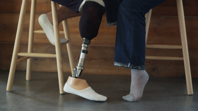 Feet and Legs of Young Japanese Couple A young Japanese couple relaxing together at home in the kitchen, drinking tea. He has a prosthetic leg. artificial limb stock videos & royalty-free footage