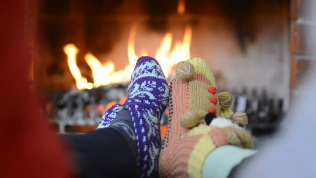 feet heated on a fireplace - calzino video stock e b–roll