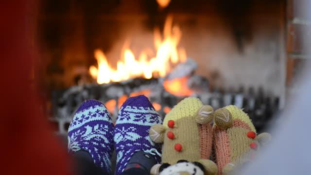 stockvideo's en b-roll-footage met voeten verwarmd op een open haard - family winter holiday