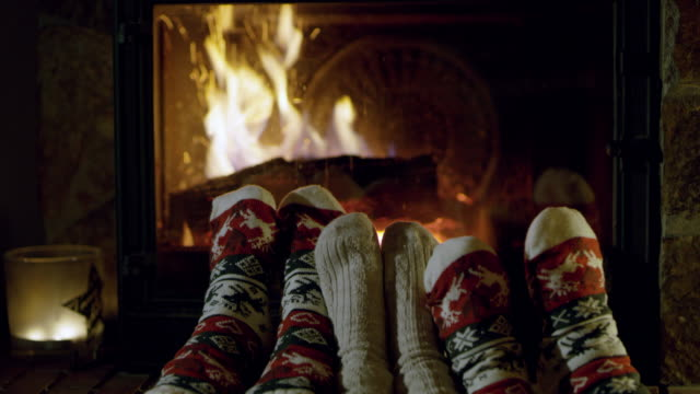 4K Feet in cozy Christmas socks relaxing by fireplace, real time video