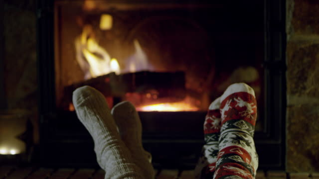 4k feet in cozy christmas socks relaxing by fireplace, real time - носок стоковые видео и кадры b-roll