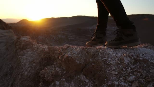 stockvideo's en b-roll-footage met voeten in wandelschoenen op de achtergrond van salar de atacama in woestijn in chili - maasvallei