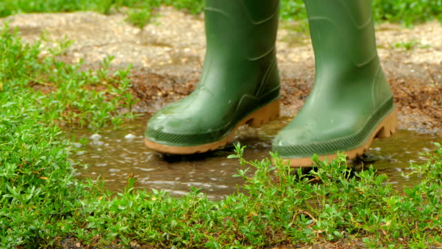 feet in rubber boots fun to jump across the puddle feet in rubber boots go into a puddle. begins to trample and jump in a puddle. Splashes fly in all directions. stamping feet stock videos & royalty-free footage