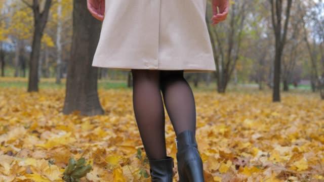 fötter dam i strumpbyxor och svarta stövlar är på hösten mattan av gult bladverk - strumpbyxor bildbanksvideor och videomaterial från bakom kulisserna