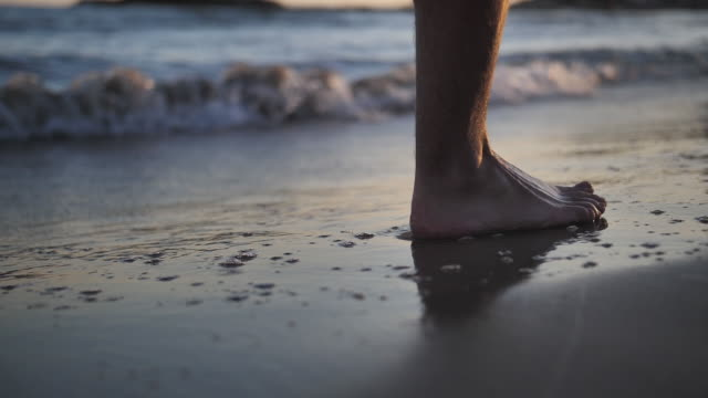 feet leaving marks on the sand near the sea, the sea washes away the marks, close up, slow motion video