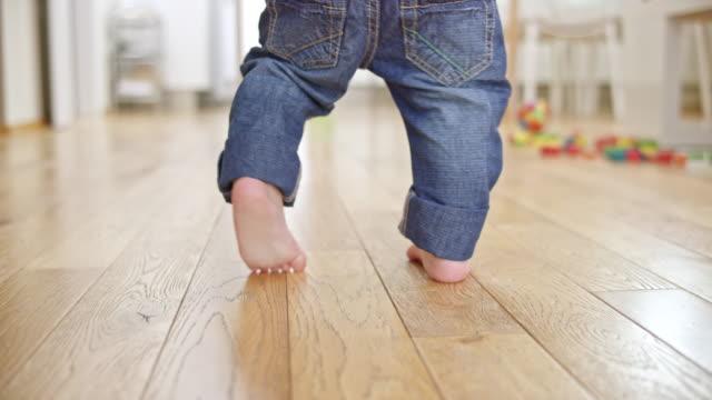vídeos de stock e filmes b-roll de slo mo feet of a baby taking his first steps - criança pequena
