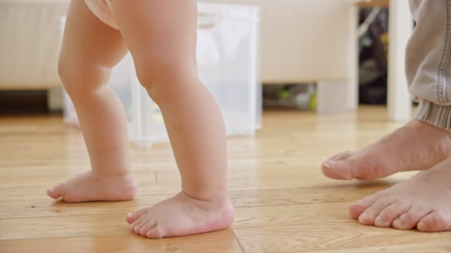 SLO MO Feet of a barefoot baby taking first steps video