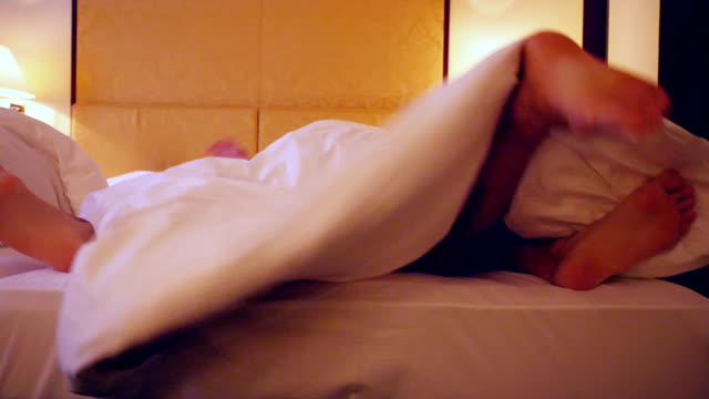 feet of a couple sharing a bed in a hotel - human sexual behavior stock videos & royalty-free footage