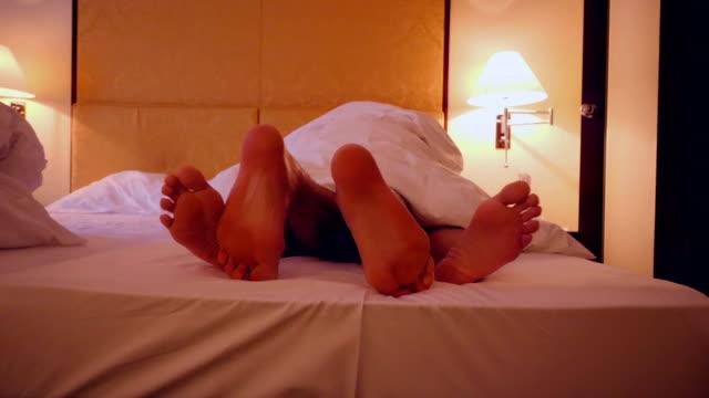 füße ein paar teilen ein bett in einem hotel - menschliches sexualverhalten stock-videos und b-roll-filmmaterial