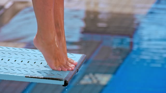 SLO MO Feet of a female diver jumping off the spring board and into the pool Slow motion medium handheld shot of the feet of a female diver diving off the spring board. Shot in Croatia. focus on foreground stock videos & royalty-free footage