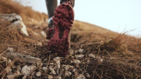 piedi slo mo di un corridore femmina che spinge ghiaia e sporcizia nell'aria - mountain video stock e b–roll