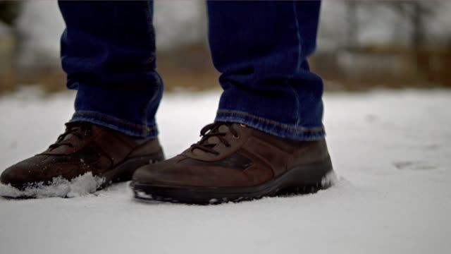 Feet of a man freezing from the cold and shifting from foot to foot Feet of a man wearing brown shoes freezing from the cold and shifting from foot to foot on the snow in winter. Man dancing trying to warm. 4K resolution video. low angle view. stamping feet stock videos & royalty-free footage