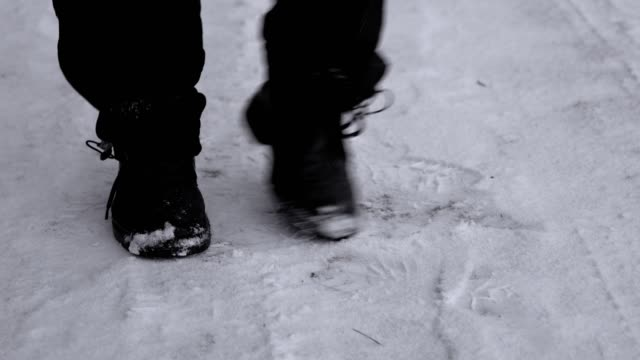Feet of a man who freezes from the cold and shifting from foot to foot Feet of a man wearing black winter shoes freezing from the cold and shifting from foot to foot on the snow in winter. A man dancing trying to warm. 4K resolution video. stamping feet stock videos & royalty-free footage