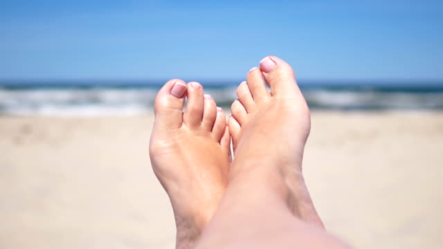 feet of a woman lying on the beach in 4k resolution slow motion 60fps - dito del piede video stock e b–roll