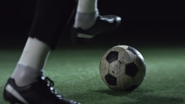 Feet of Athlete Exercising with Soccer Ball