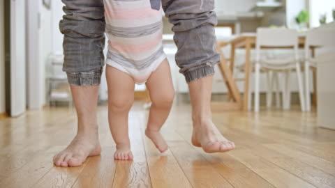 vidéos et rushes de slo mo pieds de bébé en marchant sur le bois de plancher soutenu par son père - marcher
