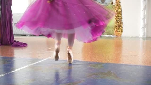 vídeos de stock e filmes b-roll de feet of ballerina on pointe shoes in purple lush skirt spinning in spacious white studio - tule têxtil