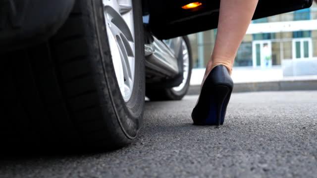 ハイヒールの黒い靴の美しい女の子の足は、自動車の後部座席に入っています。若いビジネスウーマンはドアを開けて、現代の車に入る。低角度ビュークローズアップスローモーション - 入る点の映像素材/bロール