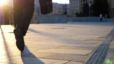 vídeos y material grabado en eventos de stock de pies de hombre de negocios con maletín caminando en la calle de la ciudad al atardecer. empresario viajando al trabajo. el tipo confiado está en su camino a la oficina. el trabajador va al aire libre. vista posterior cerrar moiton lento - negocio corporativo