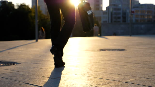 Feet of business man with briefcase walking in city street at sunset time. Businessman commuting to work. Confident guy being on his way to office. Worker going outdoor. Rear view Close up Slow moiton