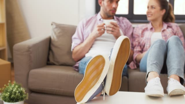 feet of couple drinking coffee at new home