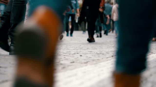 fötter av skara människor som gick på gatan i slow motion - kameraåkning på räls bildbanksvideor och videomaterial från bakom kulisserna