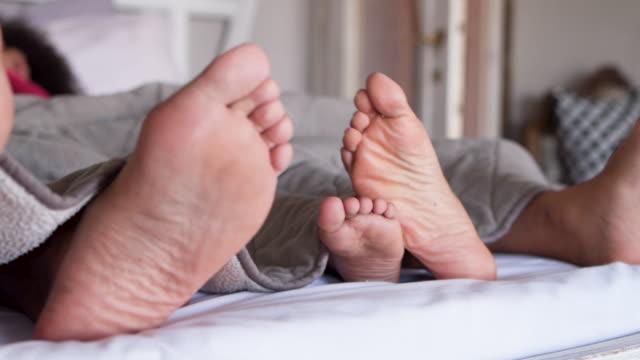 feet of family in bed - kołdra filmów i materiałów b-roll