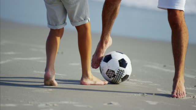 feet of hispanic father and son playing soccer - termine sportivo video stock e b–roll