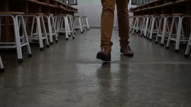 Feet of man in formal suit and leather shoes walking in corridor of the computer room full of chairs