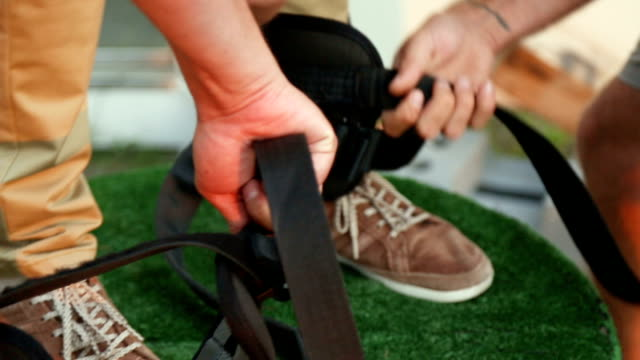 feet of man putting on safety equipment, preparing to jump from extreme heights - bungee jumping video stock e b–roll