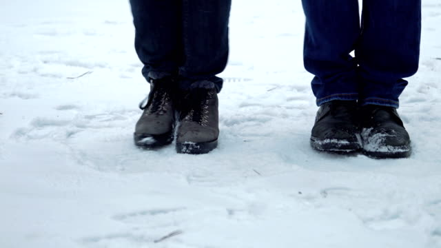 Feet of people freezing from the cold and shifting from foot to foot Feet of a man and a woman wearing shoes freezing from the cold and shifting from foot to foot on the snow in winter. People dancing trying to warm. 4K resolution video. stamping feet stock videos & royalty-free footage