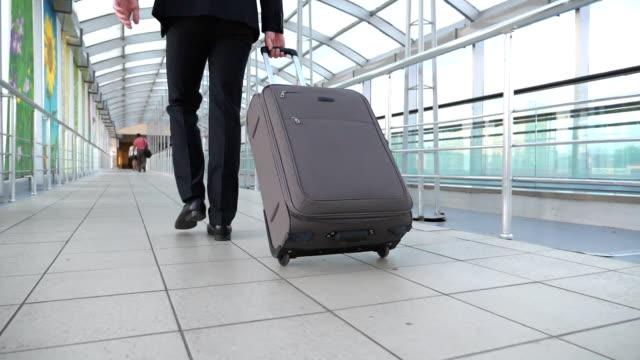 fötter framgångs rika affärs man går i hall av terminalen och dra res väska på hjul. ben av unga affärs person som går med sitt bagage inomhus. begreppet affärs resa. bakifrån slow motion - affärsresa bildbanksvideor och videomaterial från bakom kulisserna