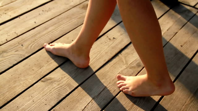 feet of the girl walking along the boardwalk on the beach video