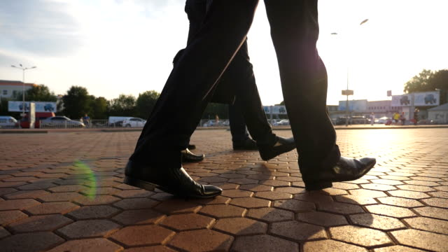 feet of three businessmen walking in city with sun flare at background. unrecognizable business men commute to work together. confident guys being on his way to office. colleagues going outdoor. slow motion close up low angle view - tre persone video stock e b–roll
