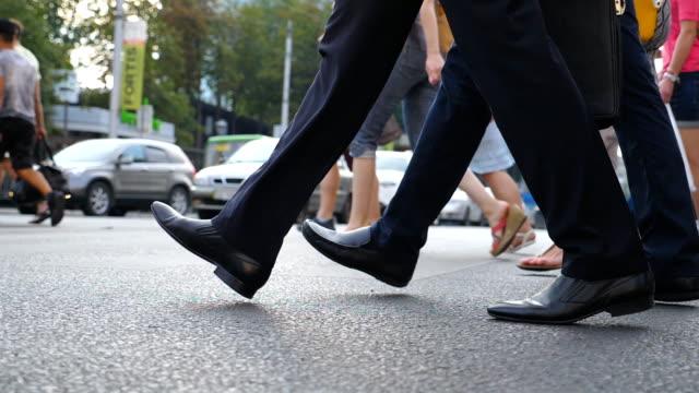 ダウンタウンの道路を横断する2人のビジネスマンの足。大都会の横断歩道を歩く男性同僚の足。若い同僚が一緒に通勤する。低角度ビュースローモーションクローズアップ - 人の脚点の映像素材/bロール
