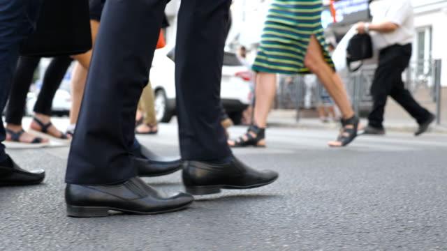 街を歩いて 2 つの認識できないビジネスマンの足。ビジネスの男性は一緒に働くために取り替えます。オフィスに彼の方法に自信を持っている男。同僚の足を移動します。スローモーションを側面図を閉じる - 後に続く点の映像素材/bロール