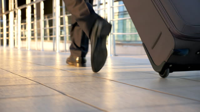 Feet of wealthy businessman walking in hall of terminal with his luggage. Legs of successful entrepreneur going indoor. Confident guy being on his way to flight. Travel concept. Back view Slow motion