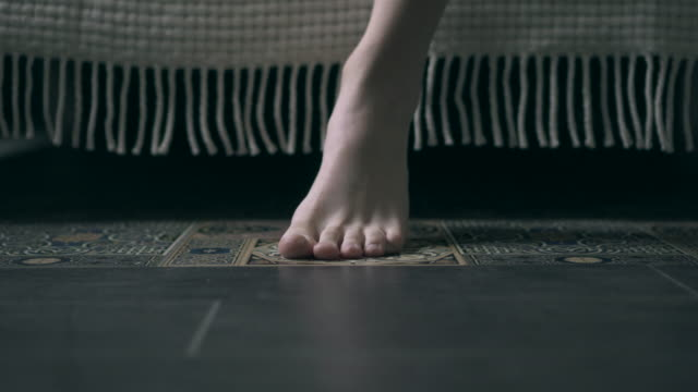 Feet of woman getting out the bed in the morning video