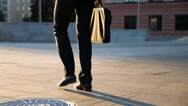 feet of young businessman with a briefcase walking in city street. business man commuting to work. confident guy in suit being on his way to work. cityscape background. slow motion rear view close up - na biegu filmów i materiałów b-roll