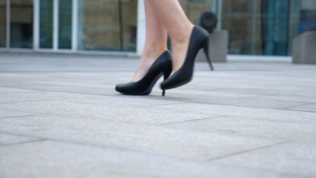 feet of young businesswoman in footwear on high-heeled going in urban street. slim female legs in black shoes on high heels walking on city. girl stepping to work. low angle view slow motion close up - ступня человека стоковые видео и кадры b-roll