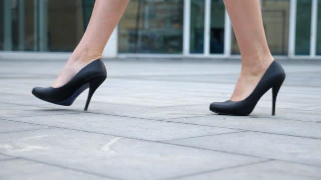 都市の通りに行くハイヒールの履物で若いビジネスウーマンの足。街を歩くハイヒールの黒い靴のスリム女性の足。女の子は仕事にステッピング。低角度ビュースローモーションクローズア� - 靴点の映像素材/bロール