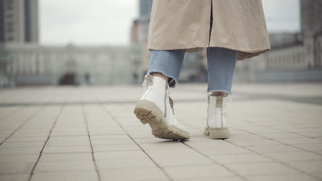 Feet of young Caucasian woman in casual clothes stomping on urban city square. Unrecognizable lady waiting outdoors on cold cloudy spring or autumn day Feet of young Caucasian woman in casual clothes stomping on urban city square. Unrecognizable lady waiting outdoors on cold cloudy spring or autumn day stamping feet stock videos & royalty-free footage