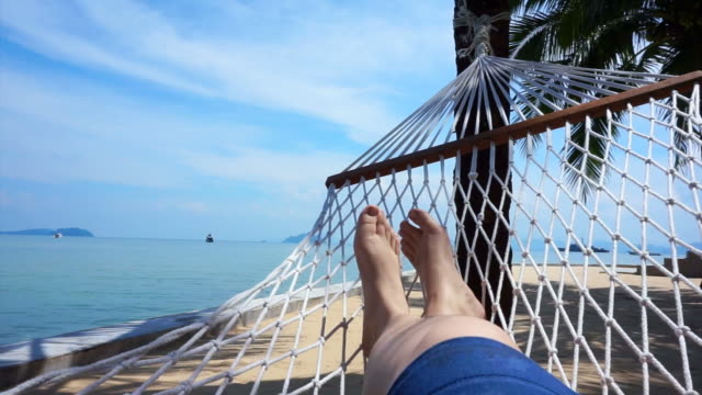 POV of Feet swinging in a hammock on coconut tree. Relaxing on the beach of Thailand video
