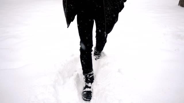 足は全身追跡ジンバルショット-若いアジア人は公園で深い雪の中を歩くために苦しんで - 都市 モノクロ点の映像素材/bロール