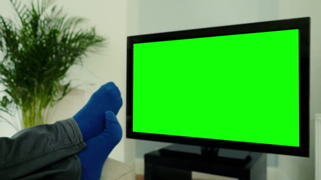 Feet up, watching chroma key TV and changing channel. video