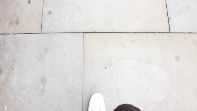 Feet walking on the street with white shoes video